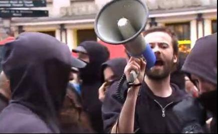 Un des dirigeants des JOC qui lance ses consignes à des manifestants cagoulés et masqués